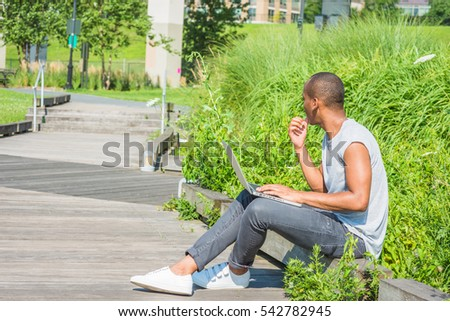 African American College Student studying in New York, wearing T shirt, black jeans, white sneakers,, sitting on wooden road on campus, working on laptop computer, thinking.