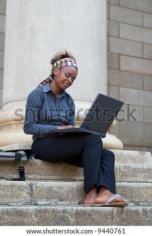 African American college student with laptop on library steps - stock photo