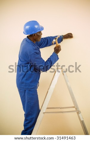 African American Construction Worker, Handyman, Carpenter, Standing on Ladder Working with Hammer