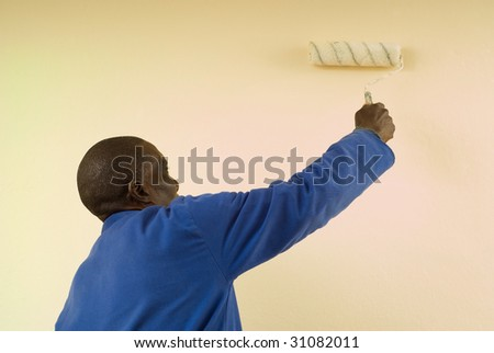 African American Construction Worker Painting a Wall