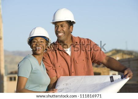 African American couple at construction site holding blueprint