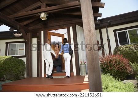 African American couple entering house - stock photo