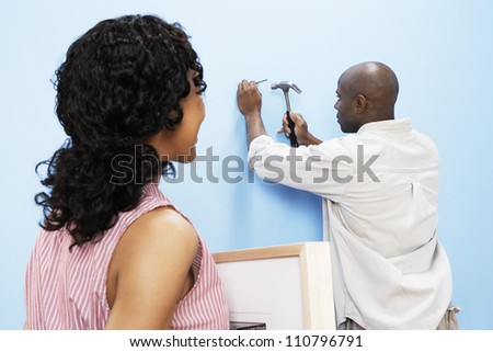 African American couple hammering nail into wall to hang picture frame - stock photo