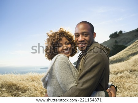 African American couple hugging in field - stock photo