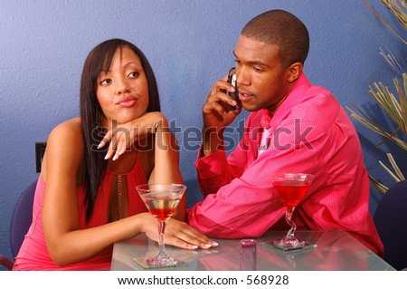 African American couple in a martini bar.Man talking on cell phone while the woman sits by annoyed and bored - stock photo