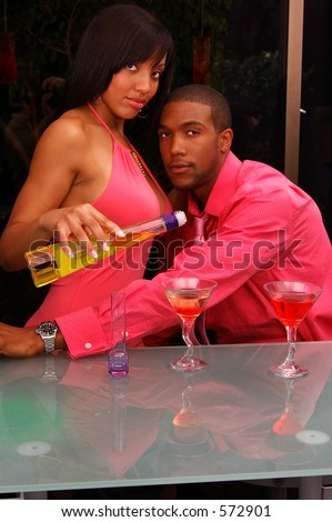African American couple in a martini bar.Woman pouring a drink - stock photo
