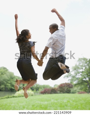African American couple jumping in air