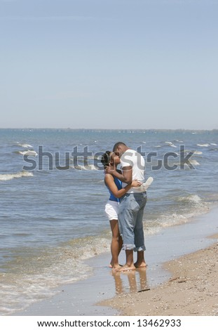African American couple kissing on the beach near the ocean plenty of copyspace - stock photo