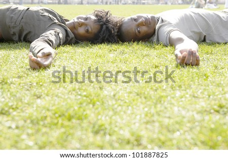 African american couple laying down on green grass in the city.