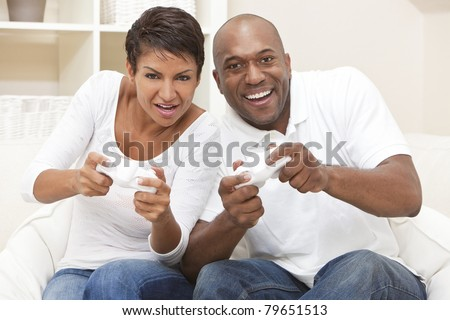 African American couple, man and woman, having fun playing video console games together. - stock photo