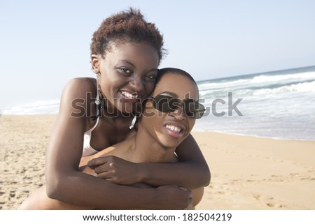 African American Couple on the beach playful and loving piggy back