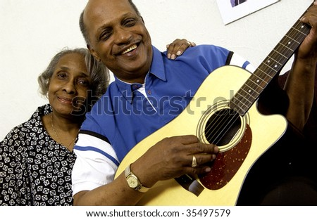 african american couple playing guitar - stock photo