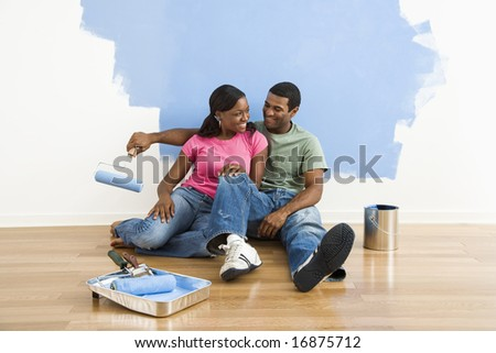 African American couple relaxing together next to half-painted wall and painting supplies. - stock photo