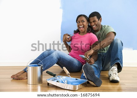 African American couple sitting together relaxing next to half-painted wall and painting supplies - stock photo