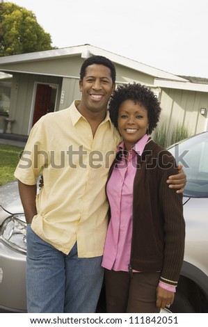 African American couple standing in front of their house - stock photo