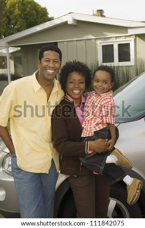 African American couple with baby standing in front of their house - stock photo