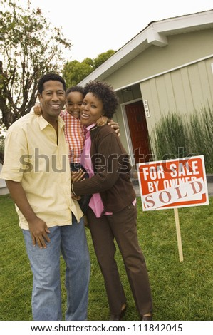 African American couple with their child standing in front of their house - stock photo