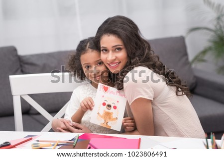 african american daughter showing greeting card for mothers day