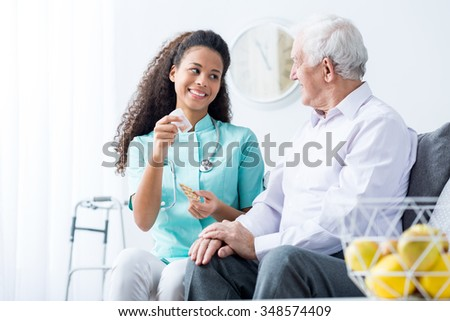 African American doctor caring about elder person - stock photo