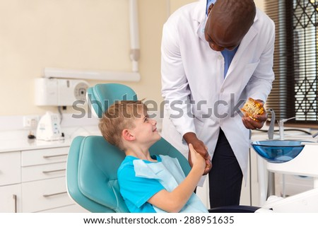 african american doctor handshaking little patient after successful operation - stock photo