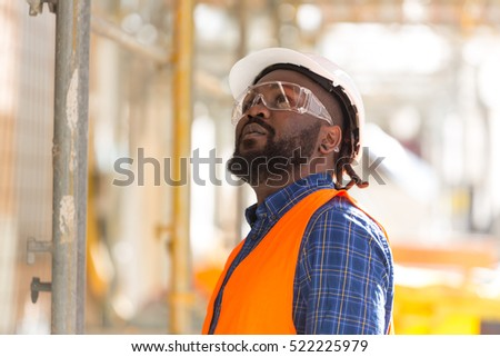African american engineer looking upwards among scaffolding