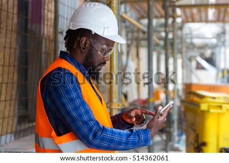 African american engineer wearing safety equipment (goggles, helmet and jacket) checking documents on tablet computer at construction site