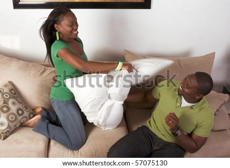 African-American ethnic black couple in pillow fight (motion blur) - stock photo