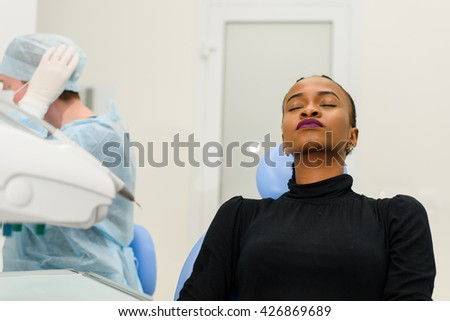 African-American ethnic black patient sitting closing eyes waiting, while her dentist preparing to operation on background