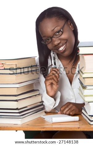 African-American ethnic black young female student in eyeglasses with pen and notepad sitting at school desk by piles of books
