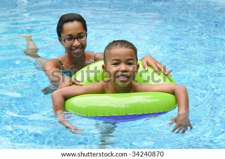 African American family in a swimming pool - stock photo