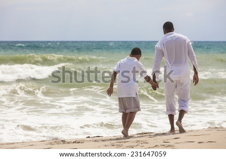 African American family of father and son, man & boy child, walking, holding hands and having fun in the sand and waves on a sunny beach - stock photo