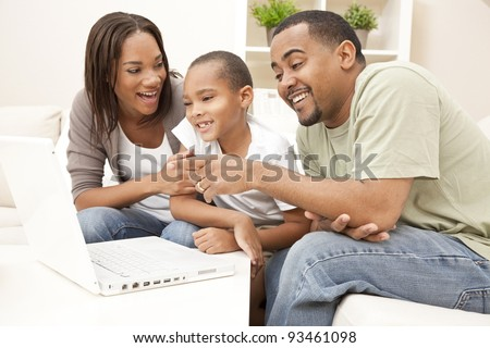 African American family, parents and son, having fun using a laptop computer together - stock photo