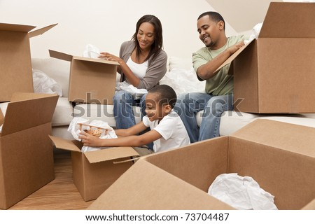African American family, parents and son, unpacking boxes and moving into a new home, The adults are unpacking crockery and houseware, the child is unpacking a toy airplane. - stock photo