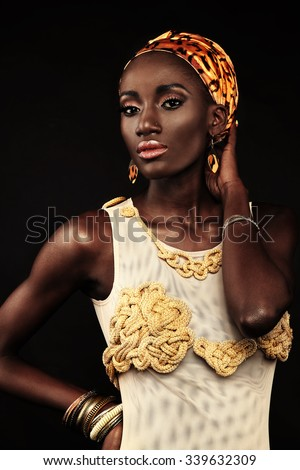 African-american fashion style. Beautiful African woman wearing headscarf and gold bathing suit handmade looking at camera while standing against black background. - stock photo