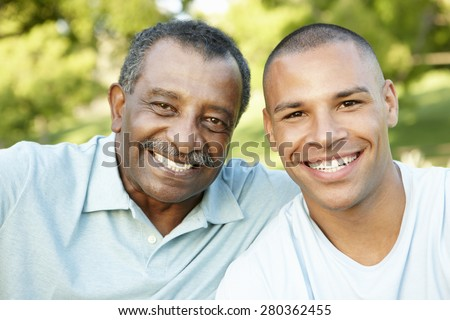 African American Father And Adult Son Relaxing In Park - stock photo