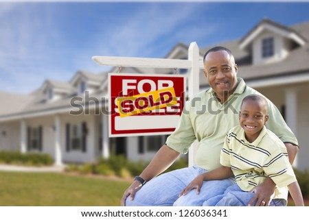 African American Father and Son In Front of Sold For Sale Real Estate Sign and New House. - stock photo