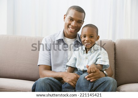 African American father and son on sofa - stock photo