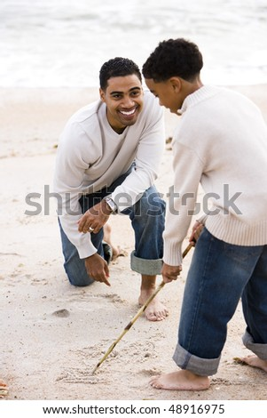 African-American father and ten year old son playing on beach - stock photo