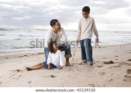 African-American father and two children playing together on beach - stock photo
