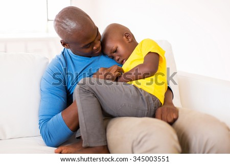 african american father comforting his ill son at home - stock photo