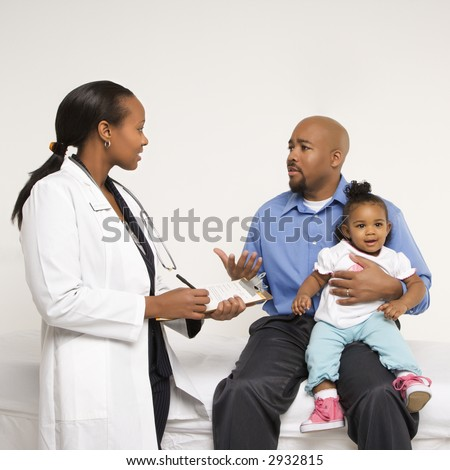 African-American father holding baby girl talking to female pediatrician.