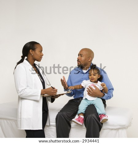 African-American father holding baby girl talking to female pediatrician. - stock photo
