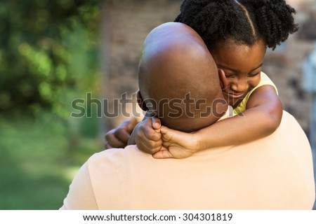African American father hugging his daughter - stock photo