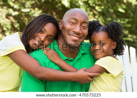 African American father hugging his daughters