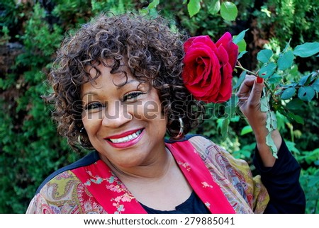 African american female beauty with a red rose outside. - stock photo