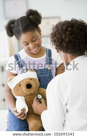 African American female doctor examining girl's teddy bear - stock photo