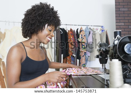 African American female dressmaker stitching cloth on sewing machine - stock photo