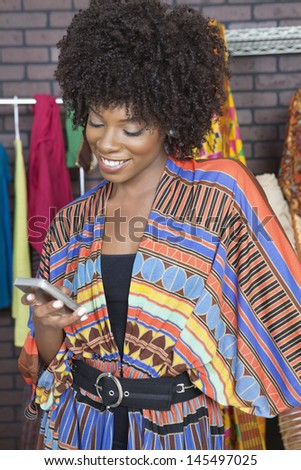 African American female fashion designer reading text message on cell phone - stock photo