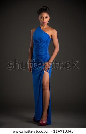 African American Female Model Portrait Low Key on Grey Background Wearing Blue Dress - stock photo