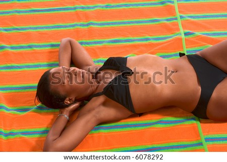 African-American female relaxing and taking sunbath on beach towel